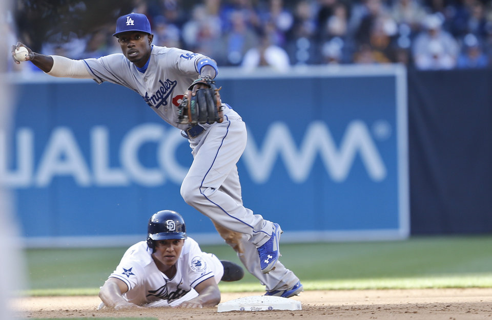 Photo - Los Angeles Dodgers second baseman Dee Gordon is unable to make a relay to first to complete a double play after the hard slide by San Diego Padres' Will Venable in the fifth inning of baseball game Tuesday, April 1, 2014, in San Diego.  (AP Photo/Lenny Ignelzi)
