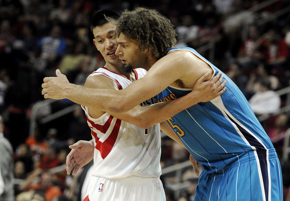 Houston Rockets' Jeremy Lin, left, and New Orleans Hornets' Robin Lopez (15) hug after Lopez fouled Lin in the second half of a preseason NBA basketball game Friday, Oct. 12, 2012, in Houston. (AP Photo/Pat Sullivan)