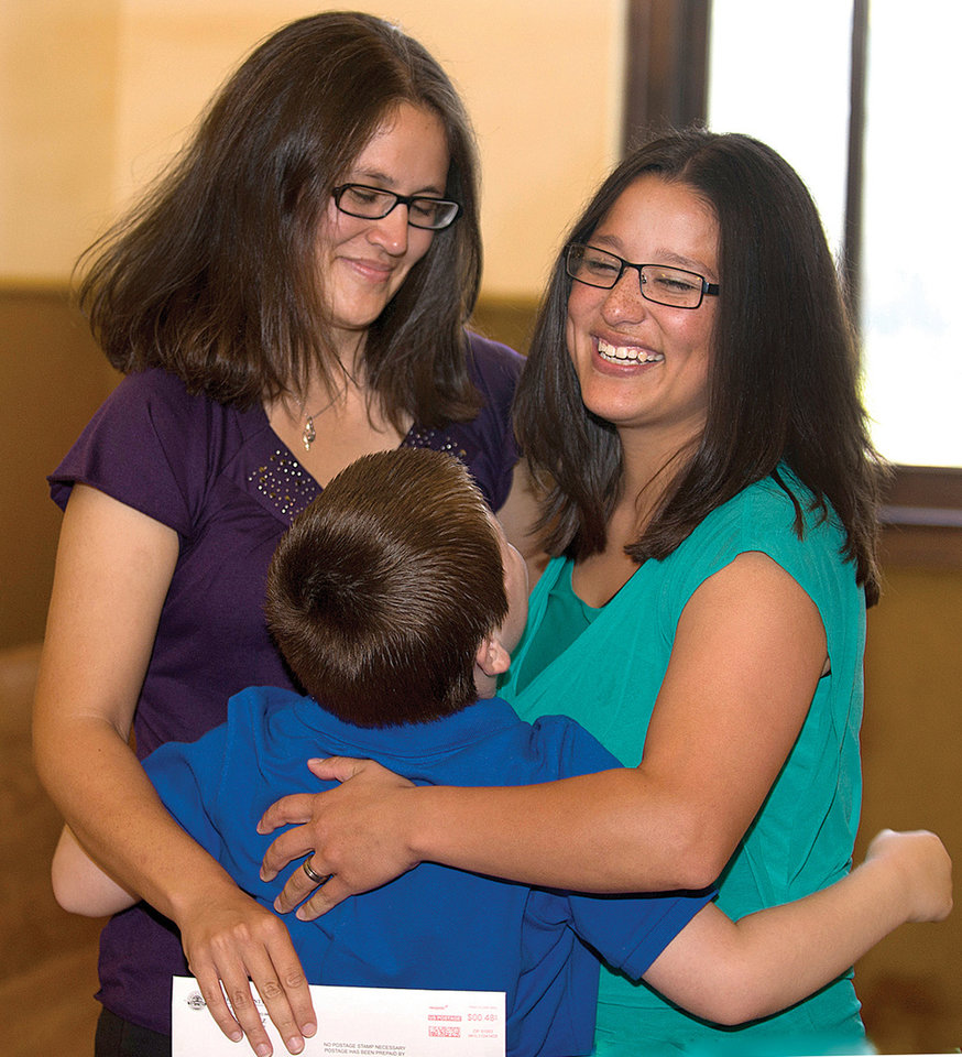 Photo - Jessie Finau, left, and Stephanie Martinez get a hug from Stephanie's nephew Uriah Martinez, 8, after receiving a marriage license at the Pueblo County Courthouse on Friday, July 11, 2014, in Pueblo,  Colo. The couple was the first in the county to receive a civil union certificate last year and were first in line again when the county clerk's opened at 8 a.m. Thursday to issue marriage licenses to same-sex couples. (AP Photo, Chris McLean/The Pueblo Chieftain)