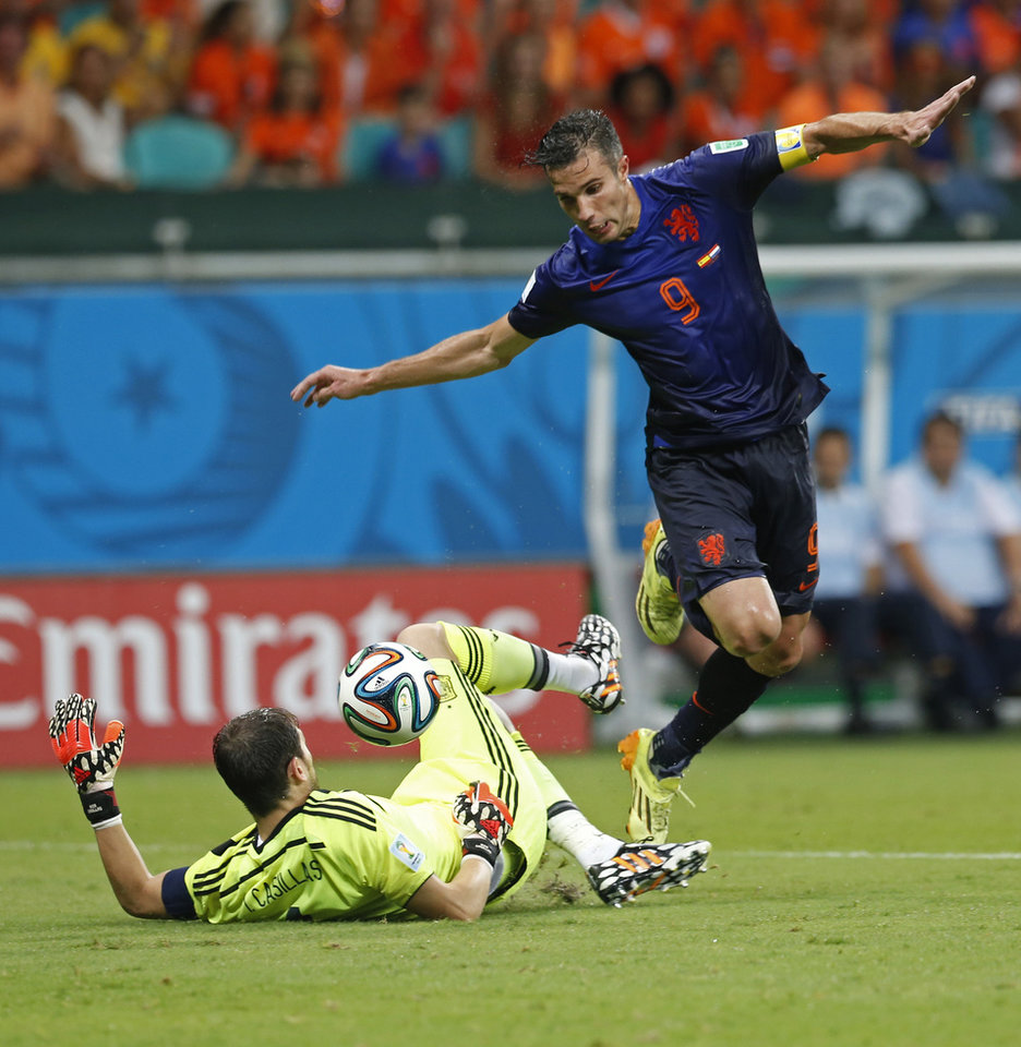 Photo - Netherlands' Robin van Persie tries to score on Spain's goalkeeper Iker Casillas during the second half of the group B World Cup soccer match between Spain and the Netherlands at the Arena Ponte Nova in Salvador, Brazil, Friday, June 13, 2014. (AP Photo/Wong Maye-E)