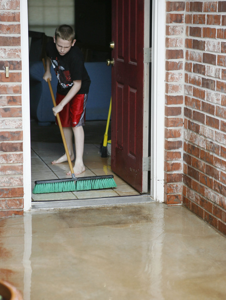 Photo - 10 year old Jake Seay helps a neighbor sweep water out of his house in the Palo Verde Addition in Edmond, OK, after flood waters inundated a number of homes in the area, Monday, June 14, 2010. By Paul Hellstern, The Oklahoman