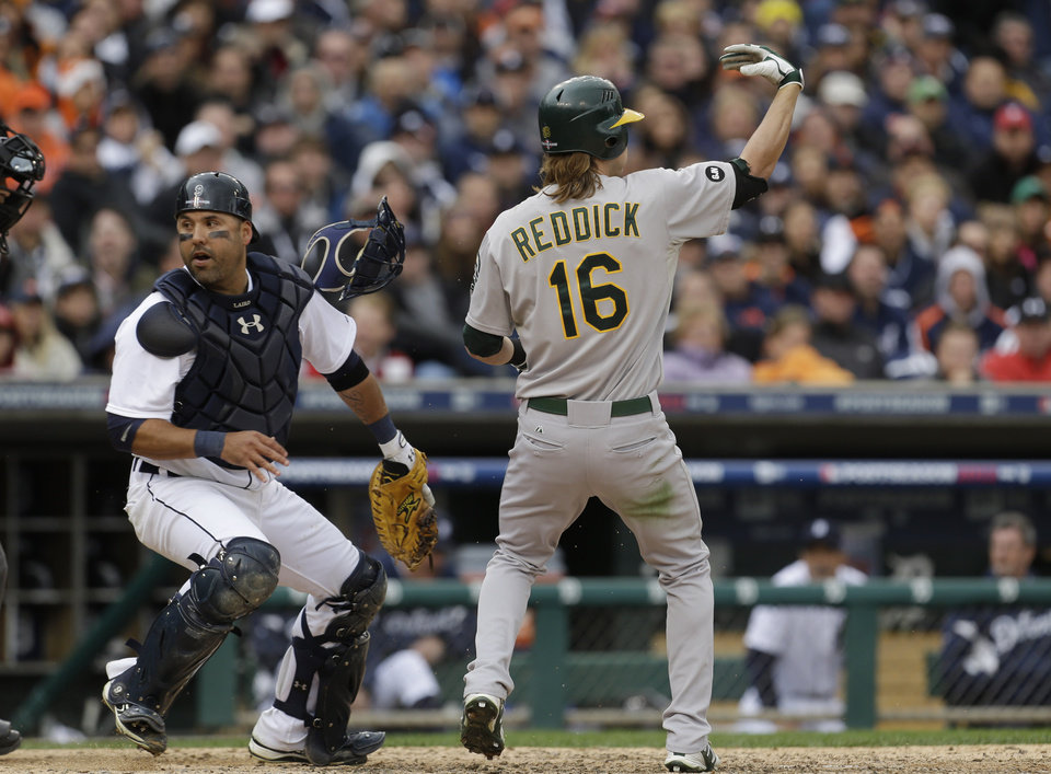 Oakland Athletics\' Josh Reddick (16) signals for teammate Yoenis Cespedes to run from third as Detroit Tigers catcher Gerald Laird chases a wild pitch during the eighth inning of Game 2 of the American League division baseball series, Sunday, Oct. 7, 2012, in Detroit. (AP Photo/Paul Sancya)