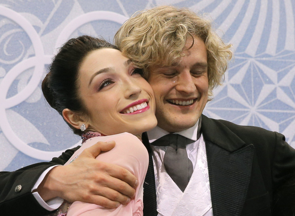 Photo - Meryl Davis and Charlie White of the United States embrace as they wait in the results area after competing in the ice dance short dance figure skating competition at the Iceberg Skating Palace during the 2014 Winter Olympics, Sunday, Feb. 16, 2014, in Sochi, Russia. (AP Photo/Vadim Ghirda)