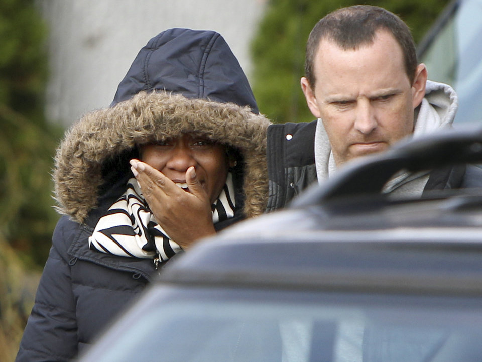 Photo - Glenda Moore, and her husband, Damian Moore, react as they approach the scene where at least one of their childrens' bodies were discovered in Staten Island, New York, Thursday, Nov. 1, 2012. Brandon Moore, 2, and Connor Moore, 4, were swiped into swirling waters as their mother tried to escape her SUV on Monday amid rushing waters that caused the vehicle to stall during Superstorm Sandy.  Police said the mother, Glenda Moore, was going to her sister's home in Brooklyn when she tried to flee the vehicle with the boys, only to have the force of the rising water and the relentless cadence of pounding waves rip the boy's small arms from her.  (AP Photo/Seth Wenig) ORG XMIT: NYSW111