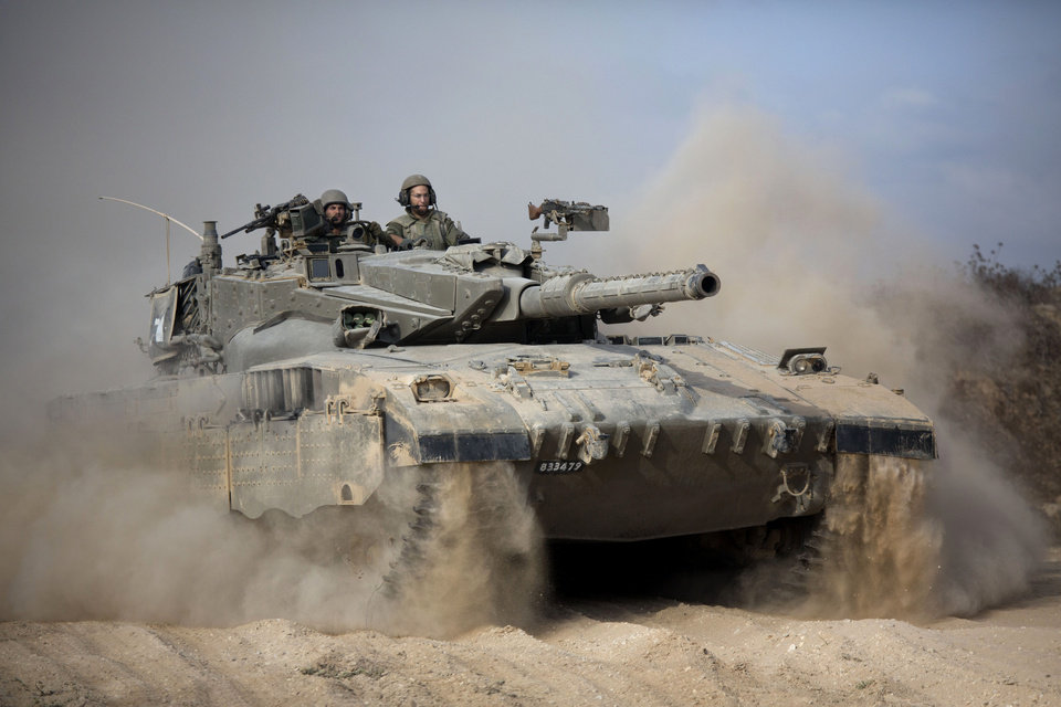 Photo - An Israeli tank moves into position near Israel and Gaza border, Friday, July, 18, 2014. Israeli troops pushed deeper into Gaza on Friday to destroy rocket launching sites and tunnels, firing volleys of tank shells and clashing with Palestinian fighters in a high-stakes ground offensive meant to weaken the enclave's Hamas rulers. Israel launched the operation late Thursday, following a 10-day campaign of more than 2,000 air strikes against Gaza that had failed to halt relentless Hamas rocket fire on Israeli cities. .(AP Photo/Dusan Vranic)