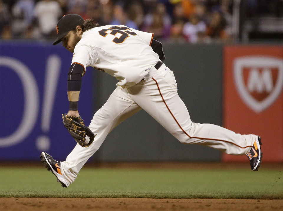 Photo - San Francisco Giants shortstop Brandon Crawford stops a ground ball hit by St. Louis Cardinals' Matt Holliday in the sixth inning of a baseball game Wednesday, July 2, 2014, in San Francisco. Crawford made the throw and Holliday was out at first base on the play. (AP Photo/Eric Risberg)