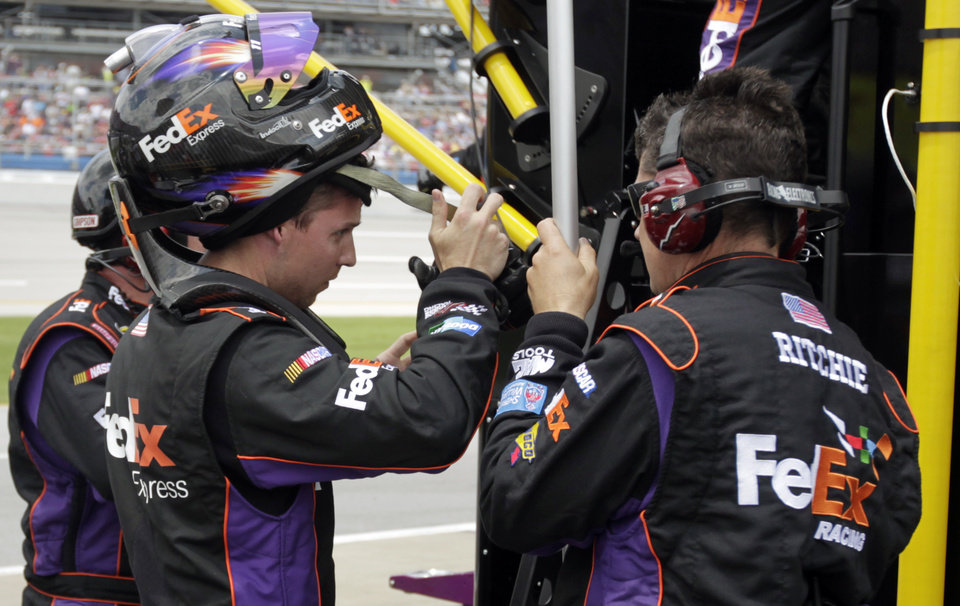 Photo - NASCAR Sprint Cup Series driver Denny Hamlin, left, talks with pit crew members after he was relieved by driver Brian Vickers on the first caution during the NASCAR Sprint Cup Series Aaron's 499 auto race at Talladega Superspeedway in Talladega, Ala., Sunday, May 5, 2013. (AP Photo/Jay Sailors)