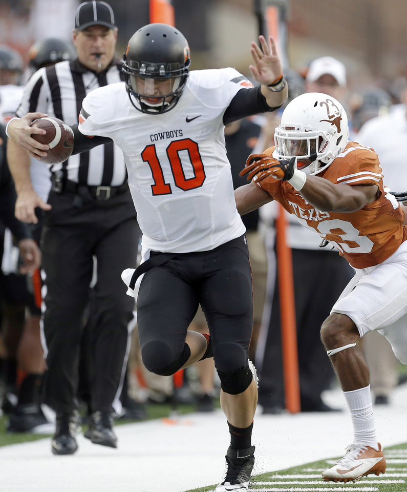 Oklahoma State's Clint Chelf (10) is forced out of bounds by UT's Carrington Byndom (23) in the third quarter during a college football game between the Oklahoma State University Cowboys (OSU) and the University of Texas Longhorns (UT) at Darrell K Royal - Texas Memorial Stadium in Austin, Texas, Saturday, Nov. 16, 2013. Photo by Sarah Phipps The Oklahoman