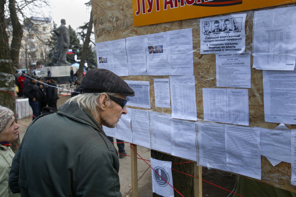 Photo - In this photo taken Tuesday, March 11, 2014, people read notices placed on an information board at a pro Russia camp set up in the town of Luhansk, eastern Ukraine, Tuesday, March 11, 2014. In 2010, the year of Ukraine's last presidential election, Luhansk gave 89% of its votes to Victor Yanukovych, a native of another town in the Donbas coal mining region. (AP Photo/Sergei Grits)