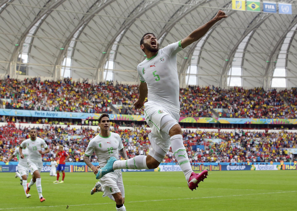 Photo - Algeria's Rafik Halliche (5) celebrates after scoring his side's second goal during the group H World Cup soccer match between South Korea and Algeria at the Estadio Beira-Rio in Porto Alegre, Brazil, Sunday, June 22, 2014. (AP Photo/Lee Jin-man)