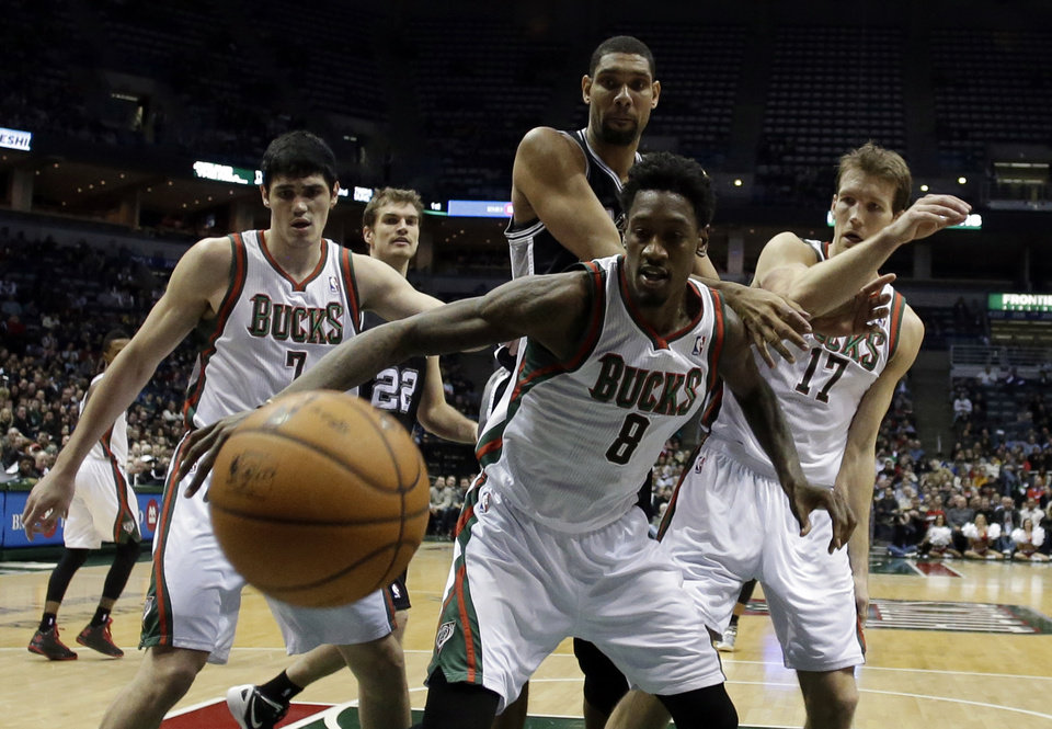 Photo - Milwaukee Bucks' Ersan Ilyasova (7), Larry Sanders (8) and Mike Dunleavy (17) go after a loose ball against San Antonio Spurs' Tim Duncan during the second half of an NBA basketball game on Wednesday, Jan. 2, 2013, in Milwaukee. (AP Photo/Morry Gash)