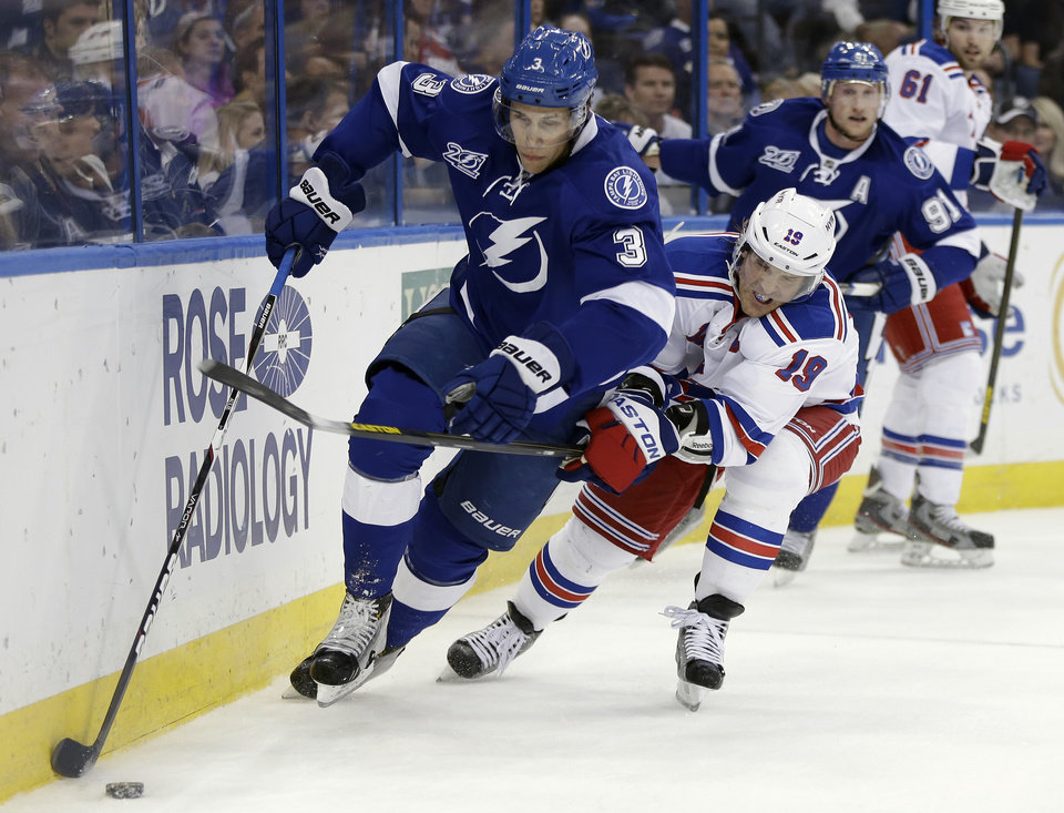 Tampa Bay Lightning defenseman Keith Aulie (3) carries the puck past New York Rangers center Brad Richards (19)  during the first period of an NHL hockey game on Saturday, Feb. 2, 2013, in Tampa, Fla. (AP Photo/Chris O'Meara)