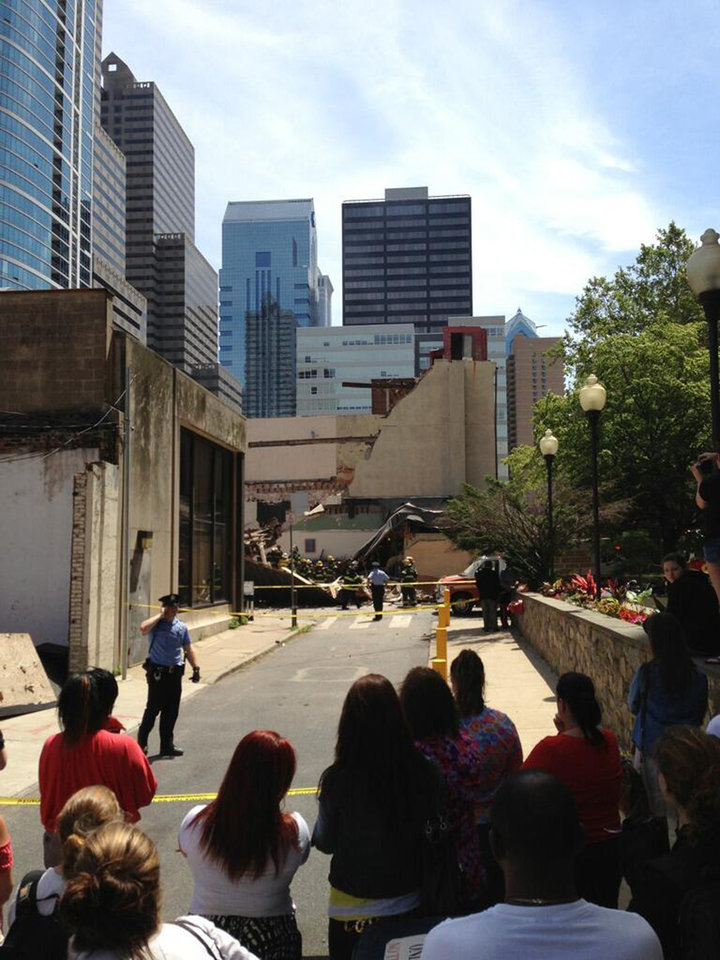 Photo - In this photo provided by Jonathan Hudson, police keep onlookers behind yellow tape near a building collapse in downtown Philadelphia, Wednesday, June 5, 2013. The city fire commissioner says as many as eight to 10 people are believed trapped in the rubble. (AP Photo/Jonathan Hudson)