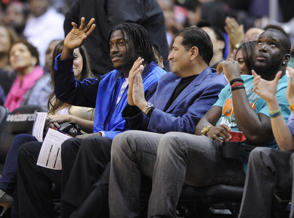 Photo - Washington Redskins quarterback Robert Griffin III waves as he attends an NBA basketball game between the Washington Wizards and the Miami Heat, Tuesday, Dec. 4, 2012, in Washington. (AP Photo/Nick Wass)