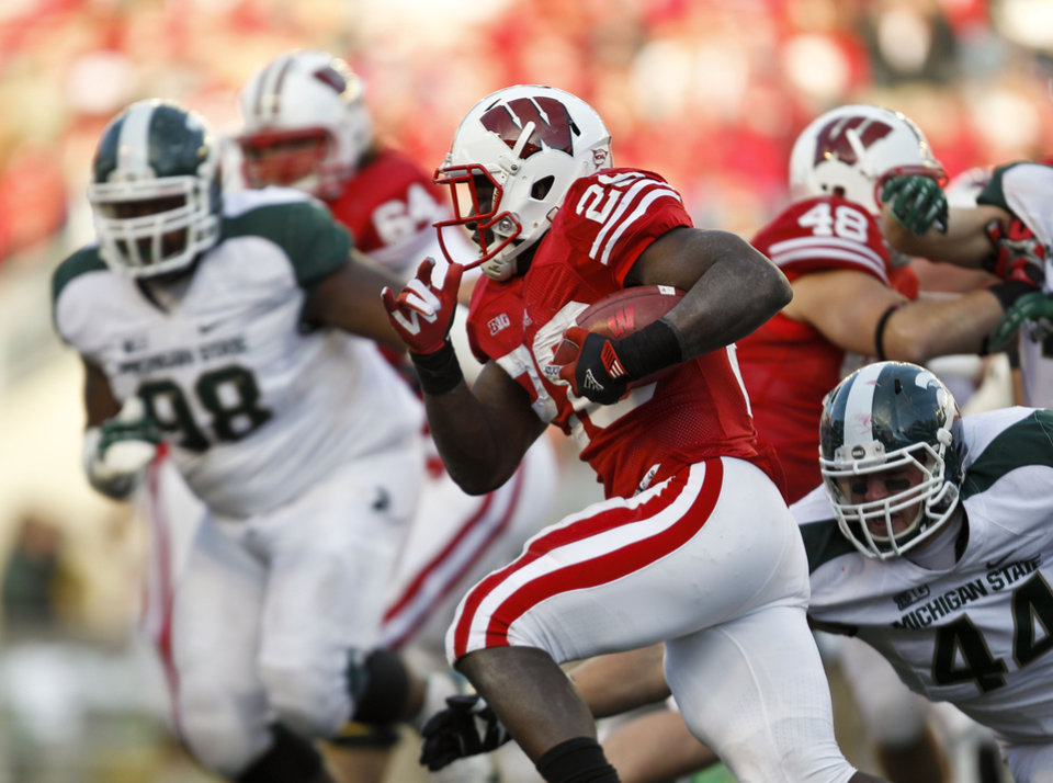Photo -   Michigan State's Anthony Rashad White (98) and Marcus Rush (44) chase Wisconsin running back Montee Ball during the second half of an NCAA college football game Saturday, Oct. 27, 2012, in Madison, Wis. Michigan State won 16-13 in overtime. (AP Photo/Andy Manis)