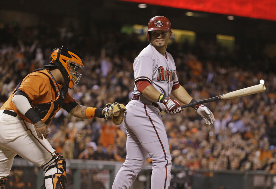 Photo - Arizona Diamondbacks' Gerardo Parra, right, strikes out swinging against San Francisco Giants starting pitcher Tim Lincecum as Giants catcher Hector Sanchez, left, makes the tag in the seventh inning of their baseball game on Friday, July 11, 2014, in San Francisco. (AP Photo/Eric Risberg)