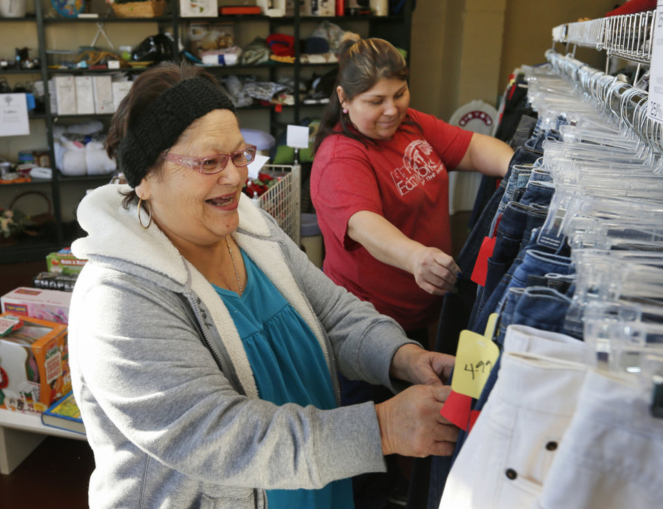 Photo - Volunteers Tere Briones, front, and Marlene Briones look through rows of items for sale at the new Shidler-Wheeler Community Thrift Store, 735 SE 15.   NATE BILLINGS - NATE BILLINGS