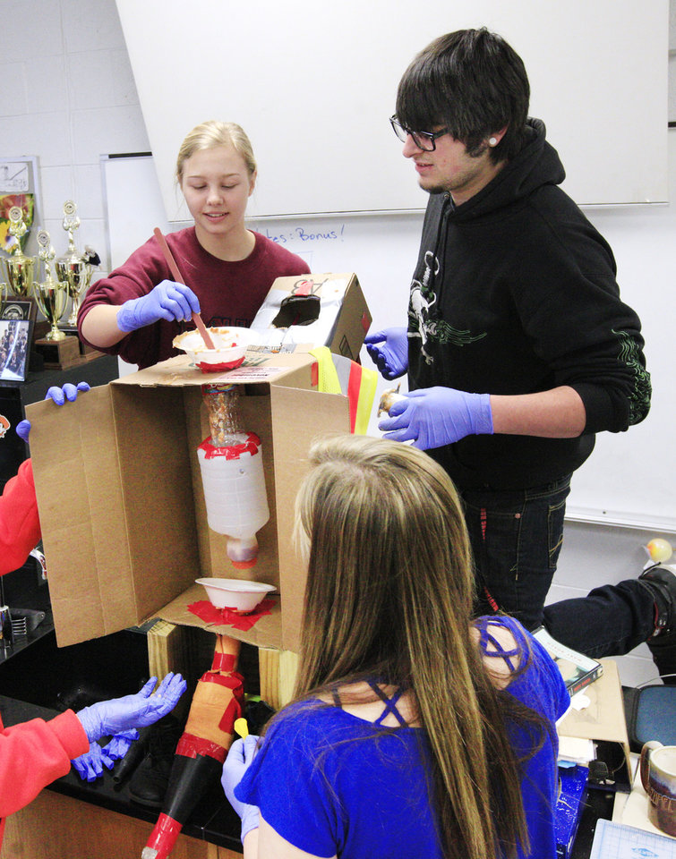Photo -      Sarai Anderson, 16, and Johnny Sexton, 17, put food particles through a digestive system they helped build for their anatomy and physiology class at Putnam City High School. Photo by Paul B. Southerland, The Oklahoman   PAUL B. SOUTHERLAND -