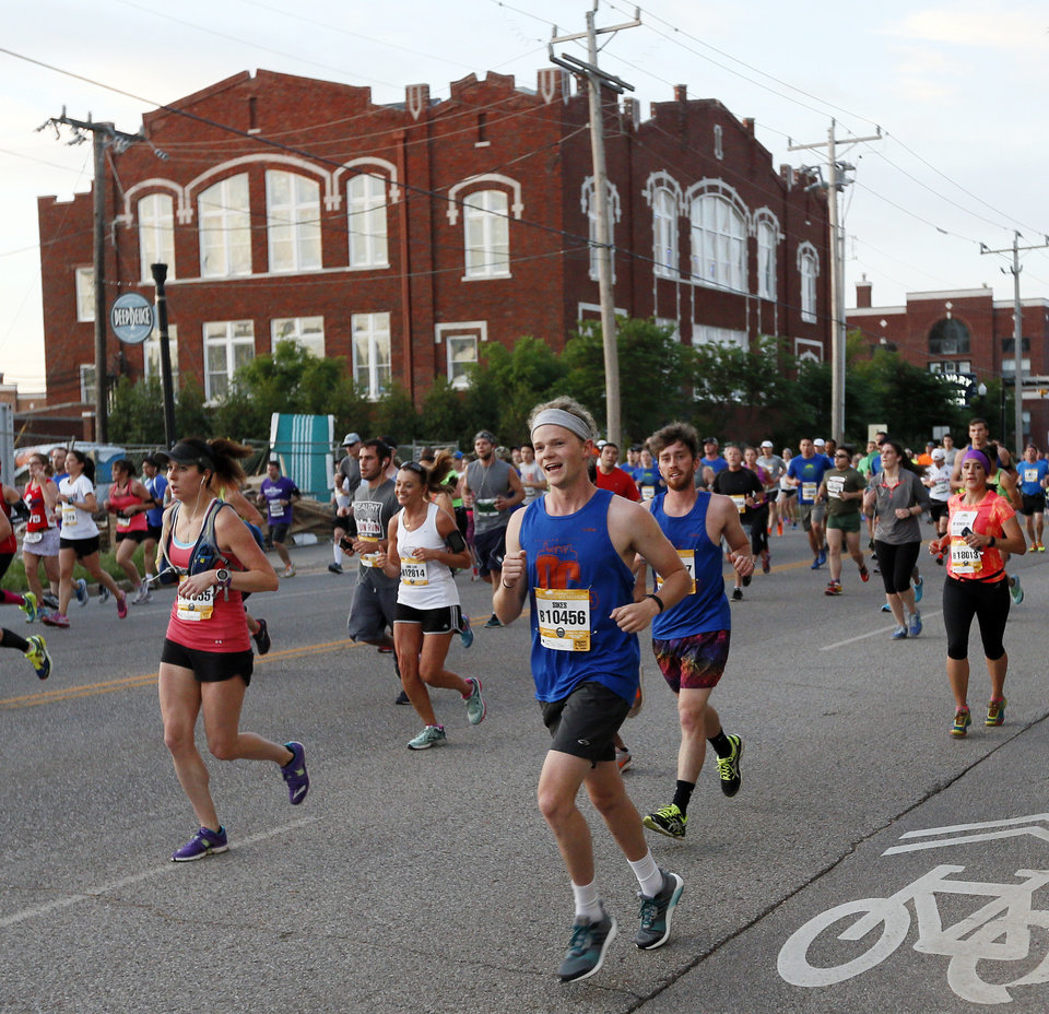 Photo - Runners travel north on Walnut Ave. during the Oklahoma City Memorial Marathon in Oklahoma City, Sunday, April 24, 2016. Photo by Nate Billings, The Oklahoman