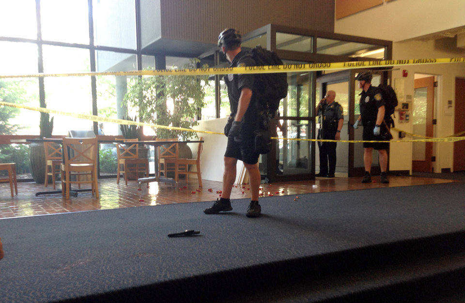 Photo - Police stand in the lobby of a building where a gunman armed with a shotgun opened fire Thursday, June 5, 2014, at Seattle Pacific University in Seattle.  A 19-year-old man was fatally shot and two other young people were wounded after a gunman entered the foyer  and started shooting.  Aaron R. Ybarra, 26, was booked into the King County Jail late Thursday for investigation of homicide, according to police and the jail roster.  (AP Photo/Jillian Smith)