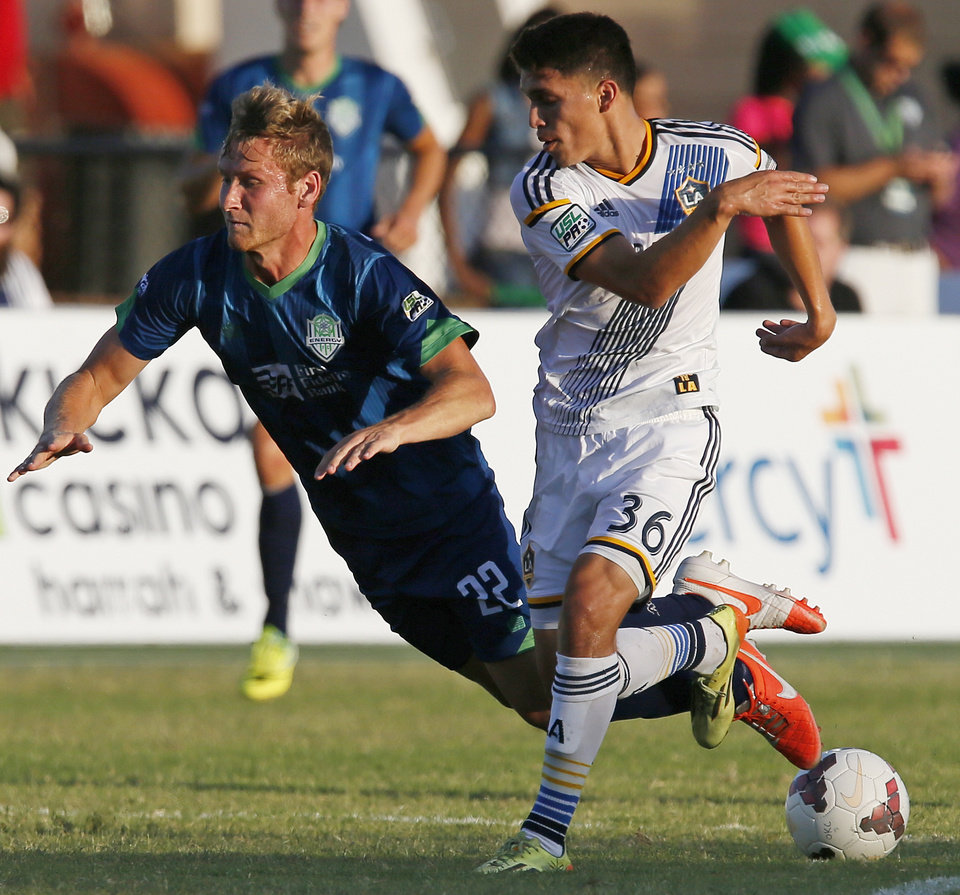 Photo - Oklahoma City's Kyle Greig (22) gets tripped up next to LA's Oscar Sorto (36) during a soccer game between the OKC Energy FC and LA Galaxy II at Pribil Stadium at Bishop McGuinness Catholic High School in Oklahoma City, Saturday, Aug. 16, 2014. Photo by Nate Billings, The Oklahoman