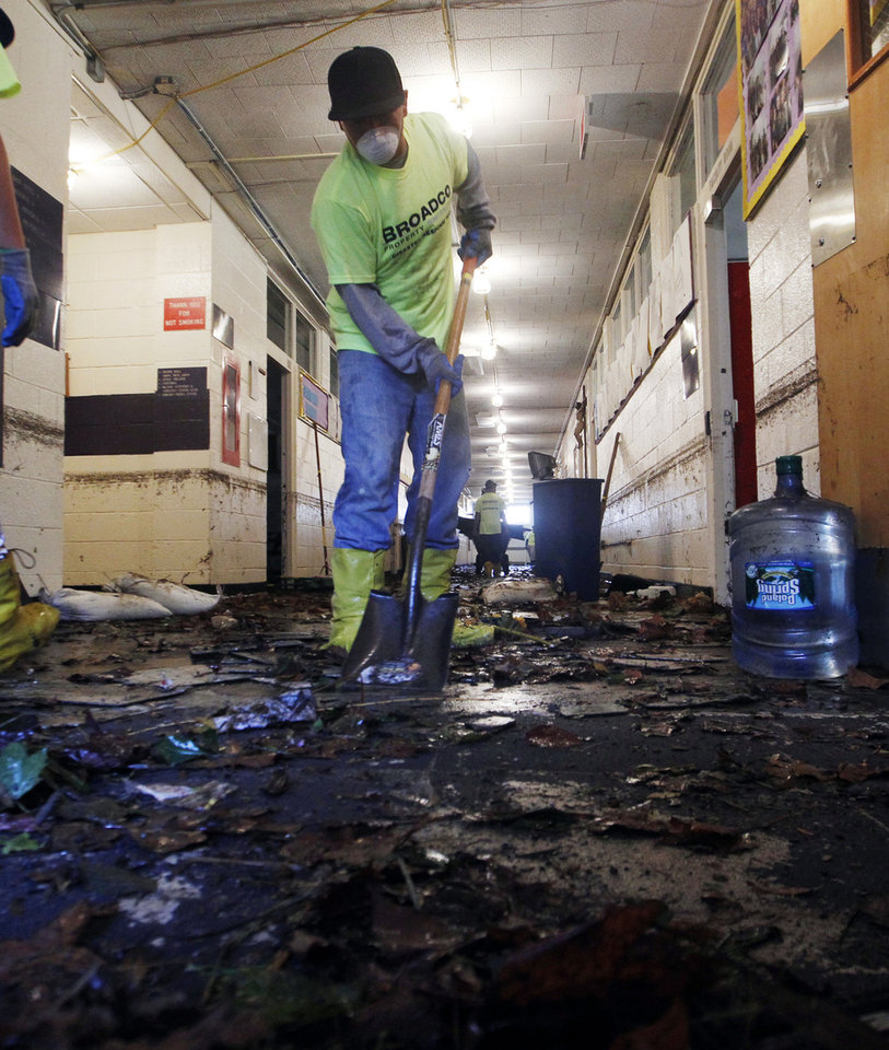 Photo -   Workers scrape up mud and tiles from flood-damaged Saint Rose High School in Belmar, N.J., Sunday, Nov. 4, 2012, as the region tries clean up the damage from Monday's storm surge by Superstorm Sandy. (AP Photo/Mel Evans)