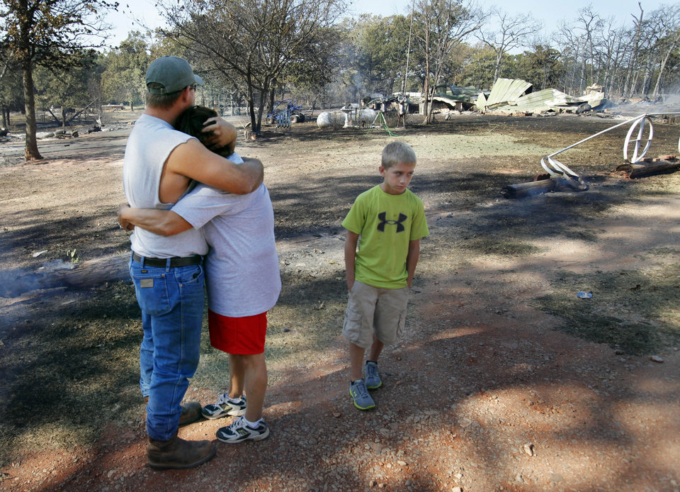 Vicky Grigg is hugged by her son Buck Grigg as they see the results of Friday's wildfire on Saturday, Aug. 4, 2012, in Slaughterville, Okla.  Grandson Gage Loyd. 10, is at right.    Photo by Steve Sisney, The Oklahoman