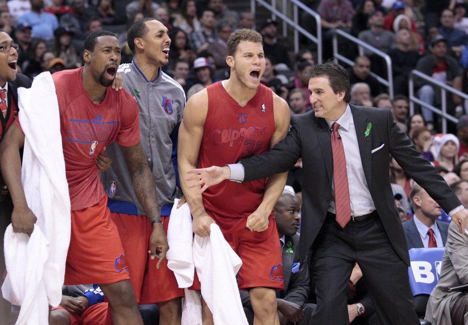 Los Angeles Clippers head coach Vinny Del Negro, tries to calm players, from left, DeAndre Jordan, Ryan Hollins and Blake Griffin at bench during the second half of their NBA basketball game against the Denver Nuggets, Tuesday, Dec. 25, 2012, in Los Angeles. The Clippers won 112-100. (AP Photo/Jason Redmond)