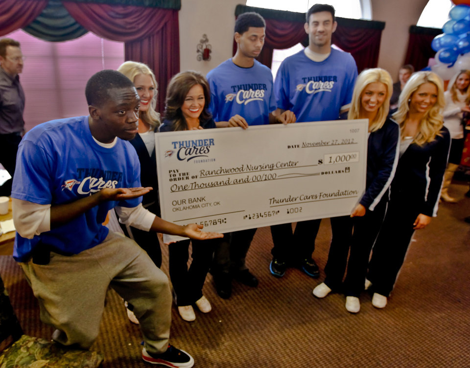 Reggie Jackson, left, along with members of the Thunder Girls, Jeremy Lamb and Nick Collison, present a check for $1,000 to the nursing home during the Oklahoma City Thunder's 1,000th community appearance at Ranchwood Nursing Home on Tuesday, Nov. 27, 2012, in Yukon, Okla. Photo by Chris Landsberger/The Oklahoman