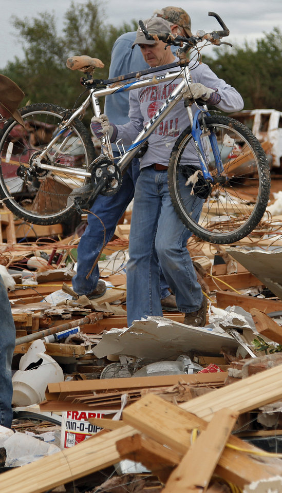 Steve Lessman helps recover items from the home of Jesse and Miranda Lewis that was destroyed by Tuesday\'s tornado west of El Reno, Wednesday, May 25, 2011. Photo by Chris Landsberger, The Oklahoman