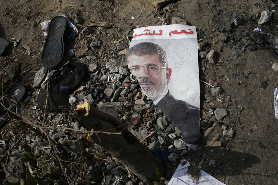 "FILE - In this Friday, Aug. 16, 2013 file photo, a trampled poster of Egypt's ousted President Mohammed Morsi is seen on the ground outside the Rabaah al-Adawiya mosque, where supporters of Morsi had a protest camp in Nasr City, Cairo, Egypt. Arabic reads, ""Yes for the legitimacy."" Almost a quarter-century ago, a young American political scientist achieved global academic celebrity by proclaiming that the collapse of communism had ended the discussion on how to run societies, leaving ""Western liberal democracy as the final form of human government."" In Egypt and around the Middle East, after a summer of violence and upheaval, the discussion, however, is still going strong.  And almost three years into the Arab Spring revolts, profound uncertainties remain. (AP Photo/Hassan Ammar, File)"