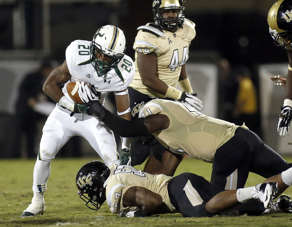 South Florida running back Marcus Shaw (20) is tackled by Central Florida linebacker Terrance Plummer (41) during the first half of an NCAA college football game on Friday, Nov. 29, 2013, in Orlando, Fla. (AP Photo/Reinhold Matay