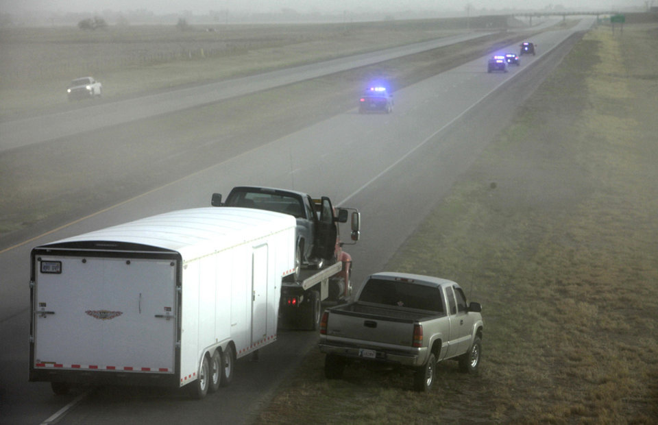 A pickup and trailer are loaded onto a wrecker Thursday after a dust storm caused crashes on Interstate 35 in far northern Oklahoma. Photo By David McDaniel, the oklahoman