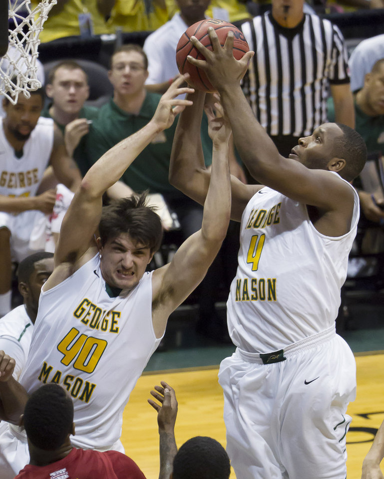George Mason forward Marko Gujanicic (40) and center Erik Copes (4) go for a rebound in the first half of an NCAA college basketball game against Iowa State at the Diamond Head Classic on Sunday, Dec. 22, 2013, in Honolulu. (AP Photo/Eugene Tanner)