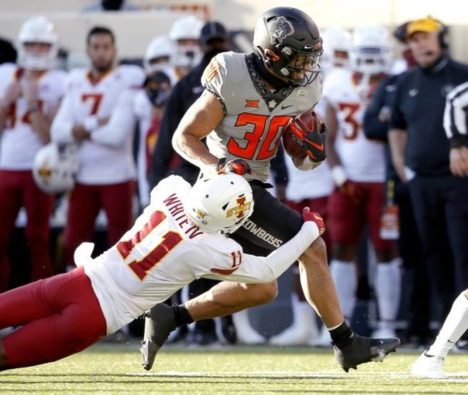 Photo -  Oklahoma State running back Chuba Hubbard, right, is tackled by Iowa State's Lawrence White IV earlier this season. [Sarah Phipps/USA TODAY Sports]