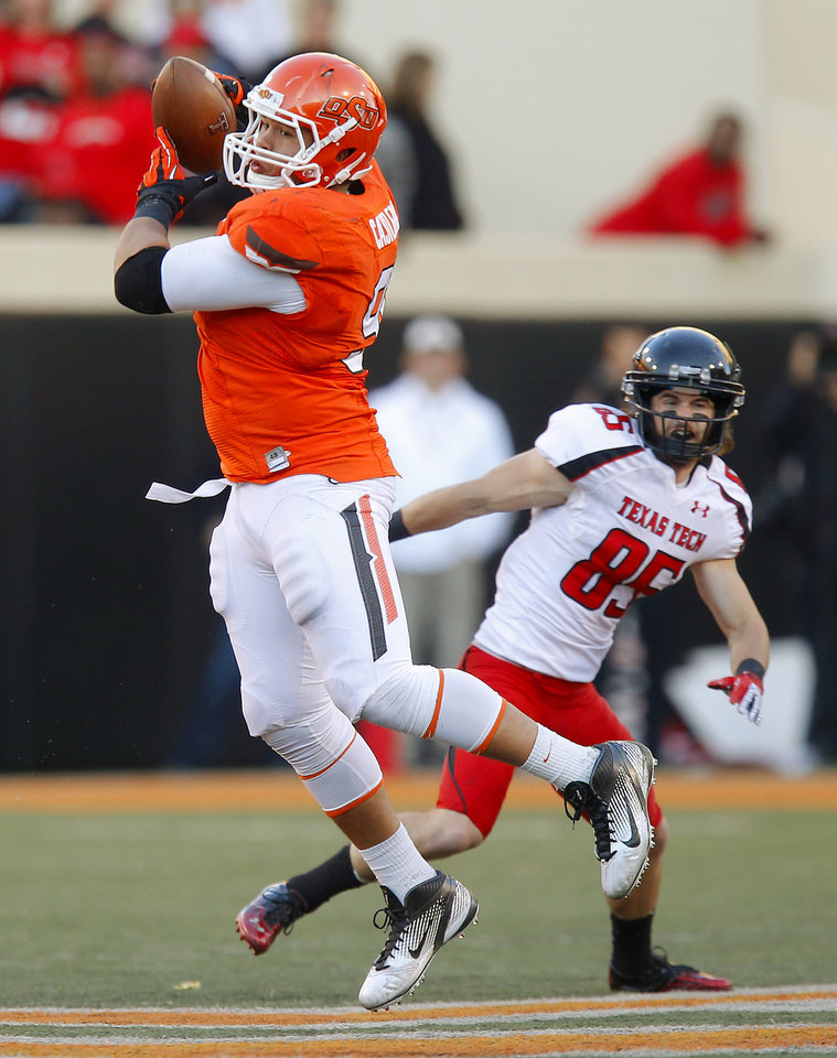 Oklahoma State\'s James Castleman (91) intercepts a pass as Texas Tech\'s Jordan Davis (85) watches during a college football game between Oklahoma State University (OSU) and Texas Tech University (TTU) at Boone Pickens Stadium in Stillwater, Okla., Saturday, Nov. 17, 2012. Photo by Bryan Terry, The Oklahoman