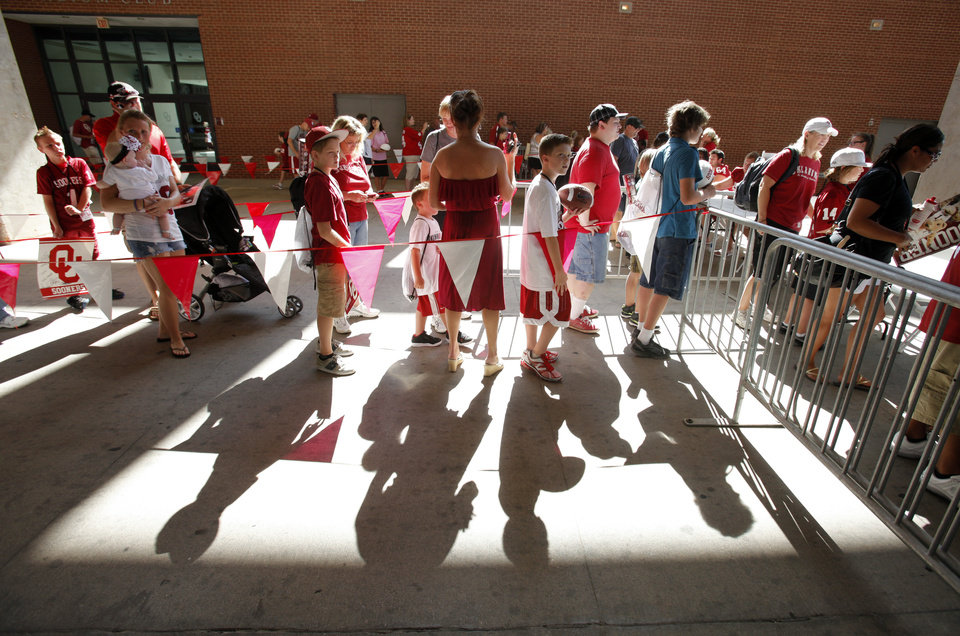 Photo - Fans stand in lines under the stands during the Meet the Sooners event inside Gaylord Family/Oklahoma Memorial Stadium at the University of Oklahoma on Saturday, Aug. 4, 2012, in Norman, Okla.  Photo by Steve Sisney, The Oklahoman