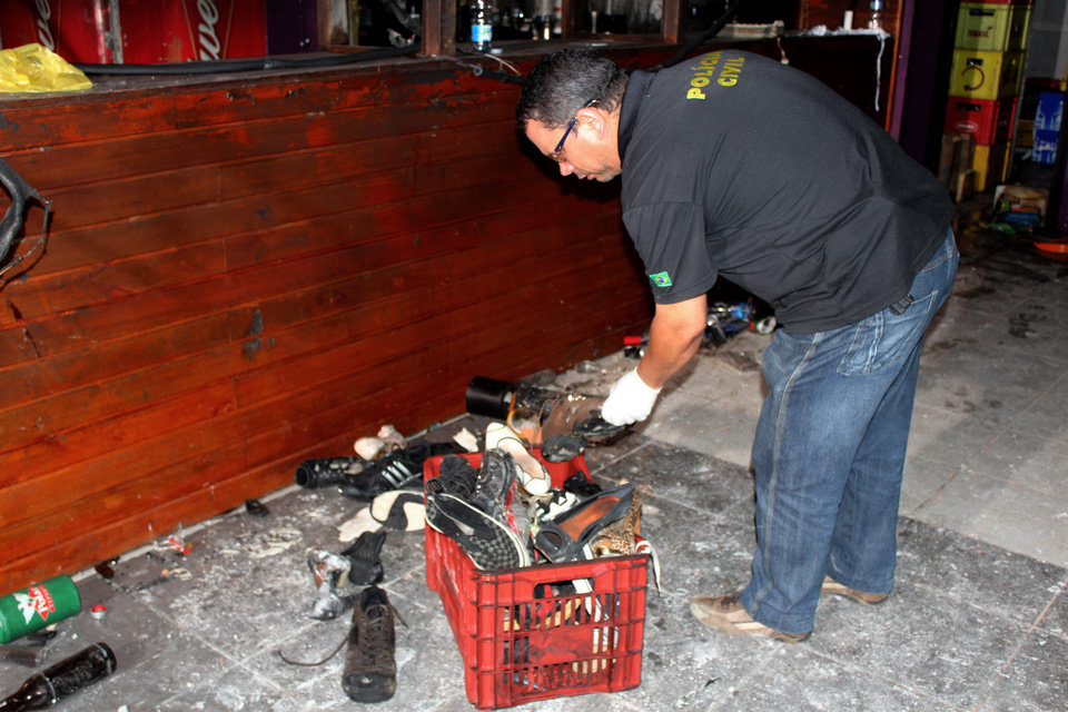 Photo - In this photo released by Policia Civil do Rio Grande do Sul, a police officer inspects victims' belongings after a fire at the Kiss nightclub in Santa Maria City, Rio Grande do Sul state, Brazil, Tuesday, Jan. 29, 2012. The blaze began at around 2:30 am local time on Sunday, during a performance by Gurizada Fandangueira, a country music band that had made the use of pyrotechnics a trademark of their shows. (AP Photo/Policia Civil do Rio Grande do Sul)