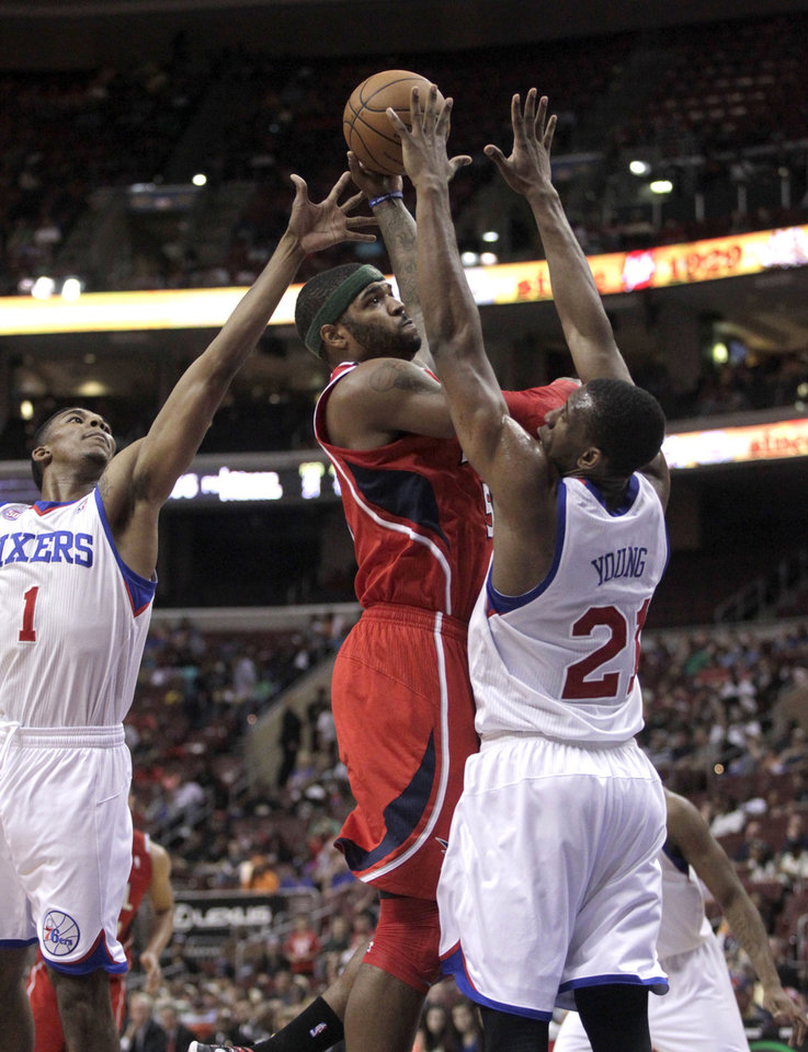 Photo - Atlanta Hawks' Josh Smith, center, shoots as Philadelphia 76ers' Nick Young (1) and Thaddeus Young (21) defend in the first half of an NBA basketball game, Wednesday, April 10, 2013, in Philadelphia. (AP Photo/H. Rumph Jr)