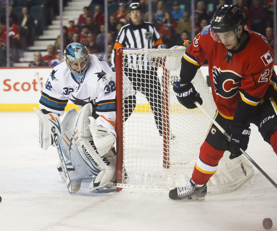 Photo - San Jose Sharks' goalie Alex Stalock, left, looks on as Calgary Flames' Sean Monahan handles the puck during first period NHL hockey action in Calgary, Monday, March 24, 2014. (AP Photo/The Canadian Press, Jeff McIntosh)