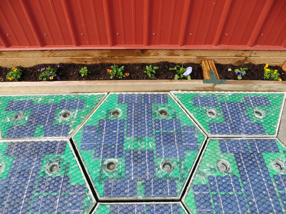 Photo - In this May 2014, photo provided by Solar Roadways, a prototype solar-panel parking area stands at the company's business in Sandpoint, Idaho. Scott Brusaw's idea for solar-powered roads has gone viral and raised more than $1.4 million in crowdsourced funding. (AP Photo/Solar Roadways)