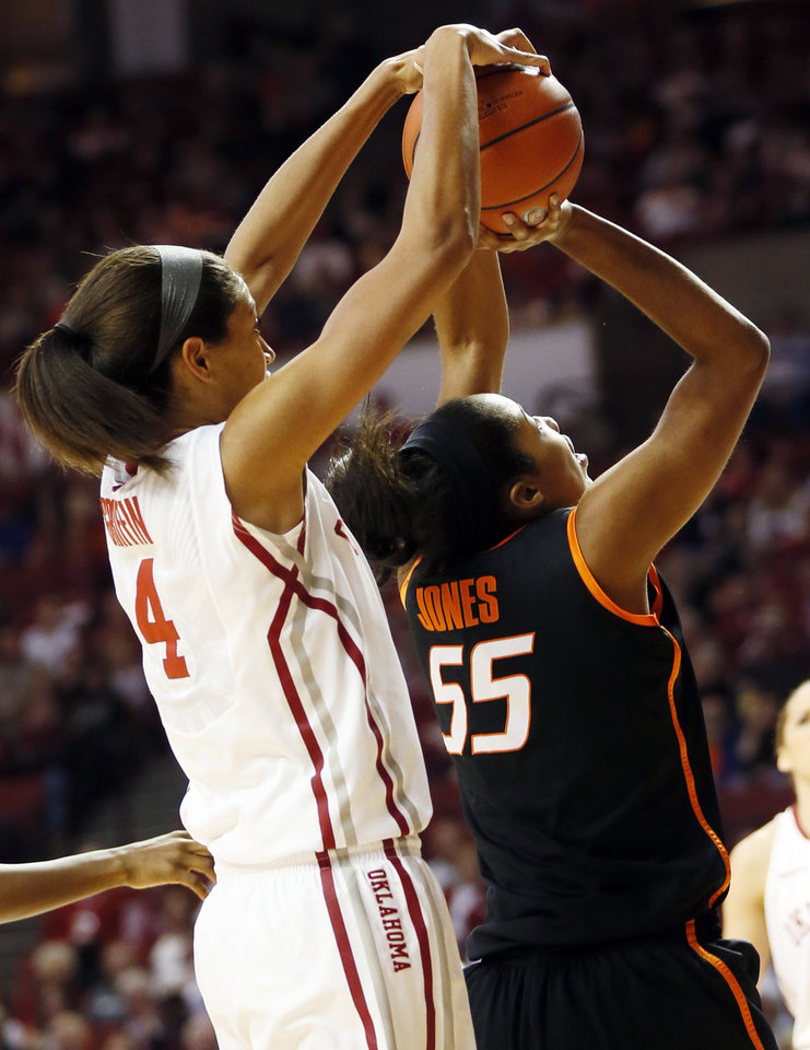 Photo - Oklahoma's Nicole Griffin (4) ties up the ball with Oklahoma State's LaShawn Jones (55) in the first half during a women's Bedlam college basketball game between the Oklahoma State University Cowgirls (OSU) and the University of Oklahoma Sooners (OU) at Lloyd Noble Center in Norman, Okla., Saturday, Feb. 1, 2014. Photo by Nate Billings, The Oklahoman
