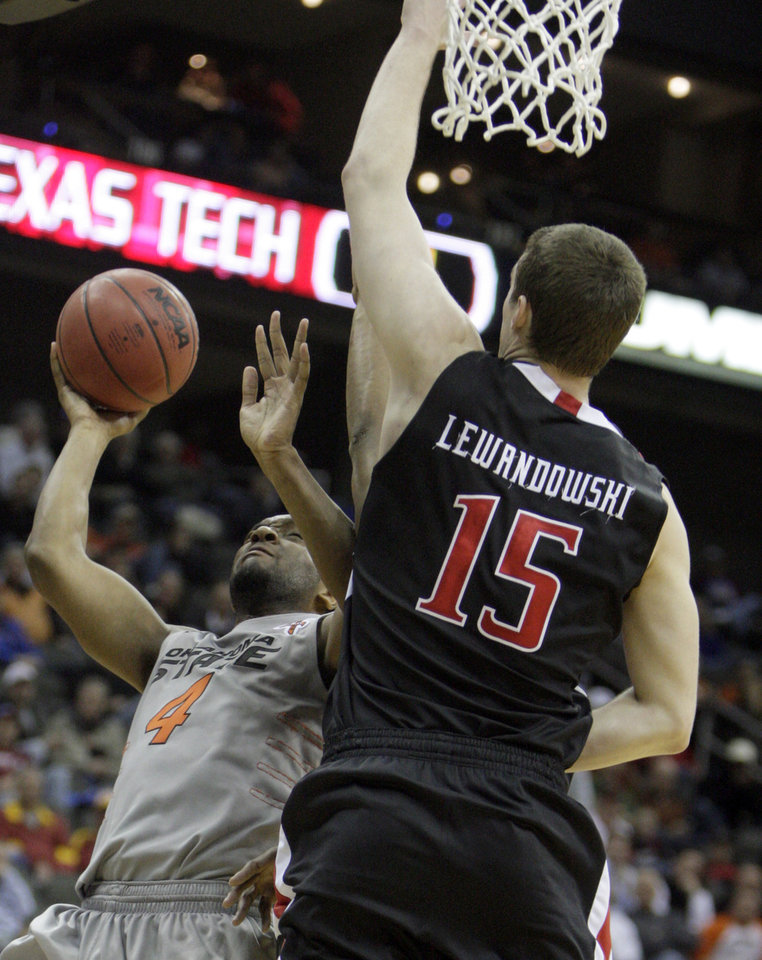 Photo - Oklahoma State's Brian Williams (4) shoots as Texas Tech's Robert Lewandowski (15) defends during the Big 12 tournament men's basketball game between the Oklahoma State Cowboys and the Texas Tech Red Raiders at the Sprint Center, Wednesday, March, 7, 2012. Photo by Sarah Phipps, The Oklahoman