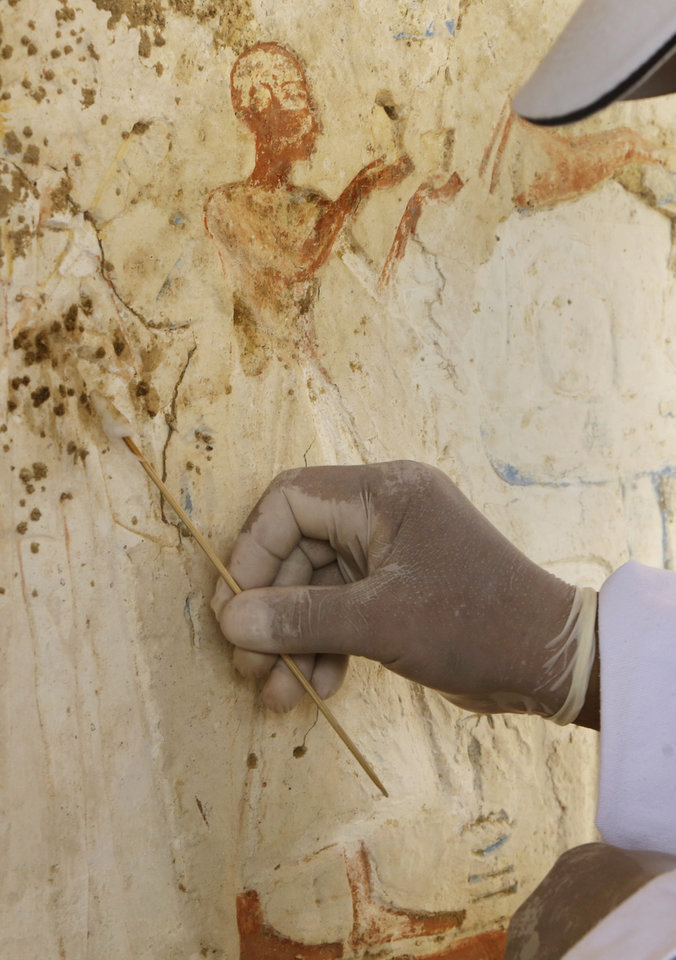 """Photo - An Egyptian conservator works at the site of a newly-discovered tomb dating back to around 1100 B.C. at the Saqqara archaeological site, 30 kilometers (19 miles) south of Cairo, Egypt, Thursday, May 8, 2014. Antiquities Minister Mohamed Ibrahim said Thursday that the tomb belongs to a guard of the army archives and royal messenger to foreign countries. Ibrahim says the Cairo University Faculty of Archaeology's discovery at Saqqara adds """"a chapter to our knowledge about the history of Saqqara."""" Saqqara was the necropolis for the ancient Egyptian city of Memphis and site of the oldest known pyramid in Egypt.(AP Photo/Amr Nabil)"""