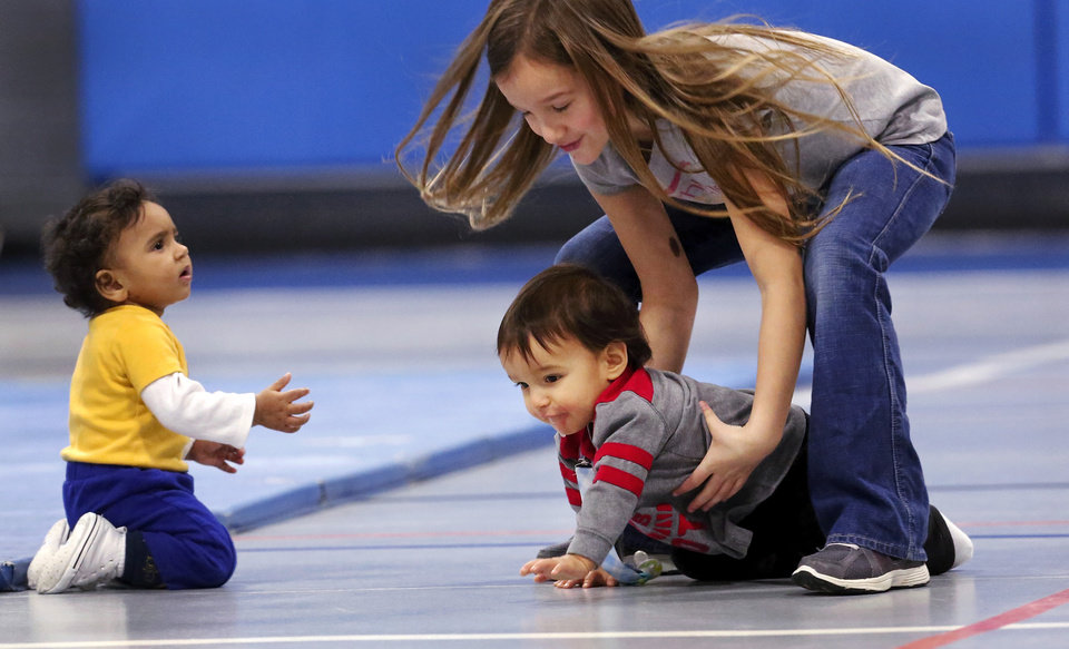 Maloree Willis, 8, scoops up contestant Maddox Cordova, 1, as he was crawling toward another competitor while they were playing on the floor after the races. Diaper Dash / Baby Crawl contest  at Jackie Cooper Gym in Yukon, Saturday, Jan. 5, 2013.  Organizers said nine entries registered to compete in the three categories. Age divisions were six to nine months old; 10 to14 months-old; and walking toddlers. Winner in the youngest category was Liam Sorrels, eight months. Winner of the middle category was Shiloh Meiki, 11 months, and the lone entrant in the walking toddler category was Cooper Ferrell, i year old. The contestants raced individually and were timed by judges. The babies were required to crawl  from one end to the other on a 20 foot mat. Quickest time was awarded first place.   Photo by Jim Beckel, The Oklahoman