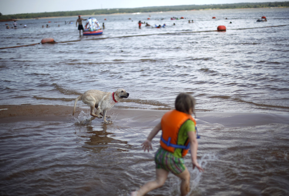 Danie Schmidt, 4 of Arcadia, Okla., plays with her dog Sadie at Arcadia Lake, Saturday, July 2, 2011. Photo by Sarah Phipps, The Oklahoman