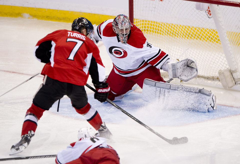 Photo - Carolina Hurricanes Andrei Loktionov slides along the ice behind Ottawa Senators Kyle Turris as he tries to score on goalie Cam Ward during second period NHL action Monday March 31, 2014 in Ottawa.  (AP Photo/The Canadian Press, Adrian Wyld)