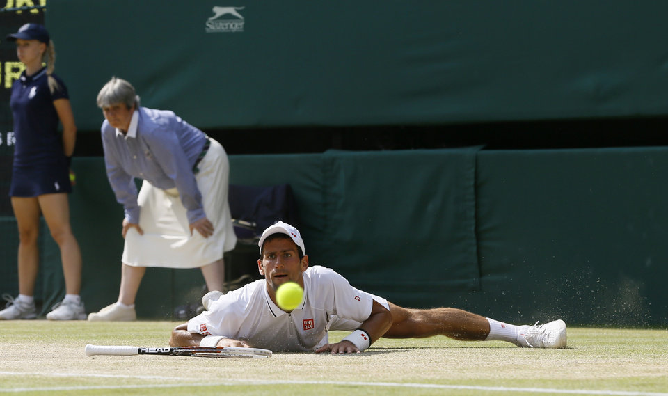 Photo - Novak Djokovic of Serbia looks at the ball after slipping as he plays Andy Murray of Britain during the Men's singles final match at the All England Lawn Tennis Championships in Wimbledon, London, Sunday, July 7, 2013.(AP Photo/Kirsty Wigglesworth)
