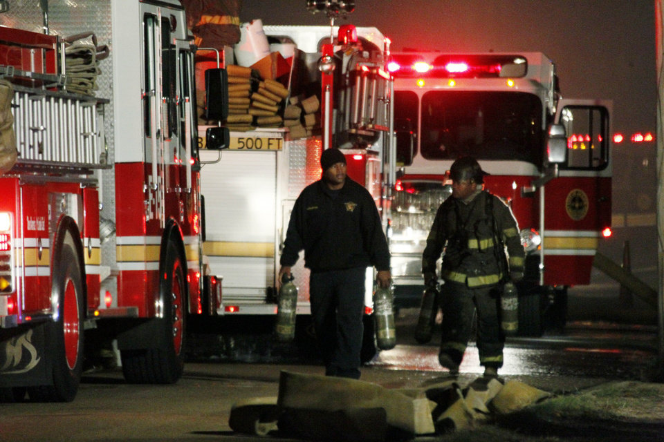 Photo -   Fire fighters begin to clean up site at a west Jackson, Miss., home where authorities say a small plane carrying three people crashed shortly after 5 p.m. Tuesday evening, Nov. 13, 2012. The home's resident is believed to have escaped but authorities have not released names of plane's passengers. (AP Photo/Rogelio V. Solis)