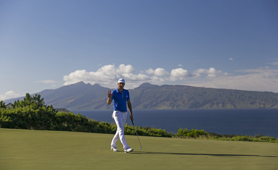 Photo - Dustin Johnson waves to the gallery on the 14th green during the third round of the Tournament of Champions golf tournament, Sunday, Jan. 5, 2014, in Kapalua, Hawaii. (AP Photo/Marco Garcia)